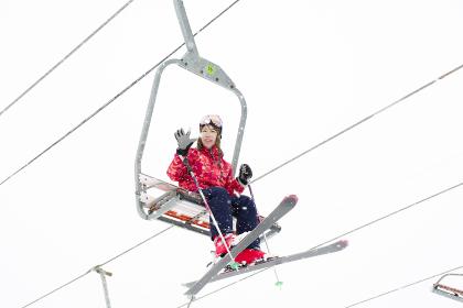 スキー場のリフトから手を振る女性