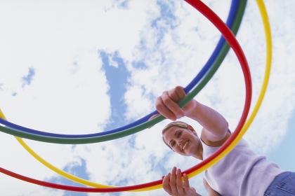 Strandszene, Portrait, Halbfigur, blonde Frau, 25 Jahre, bekleidet mit weissem T-Shirt und Jeans, spielt mit 4 bunten Gymnastik Reifen vor blauem Himmel