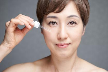 美容液を顔に当てる中年の日本人女性