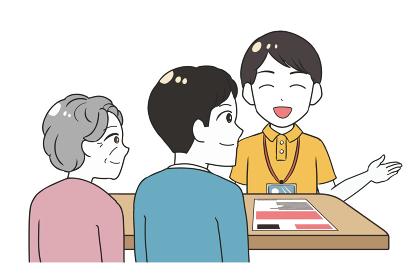 笑顔で説明する男性介護士 祖母と息子