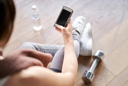スマートフォンでトレーニングアプリを見るアジア人女性