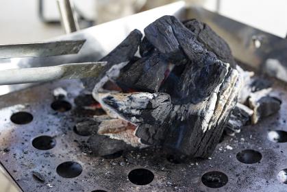 炭火焼バーベキューグリルとトングの画像