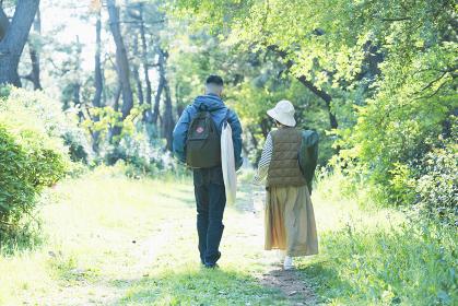 荷物を持ってキャンプ場に向かう男女
