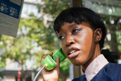 公衆電話で電話をする女性