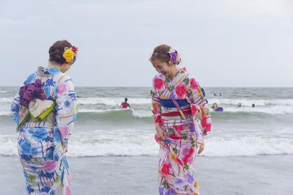 波打ち際で遊ぶ二人の浴衣の女性