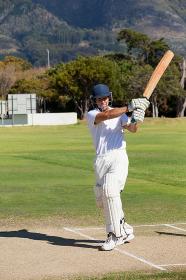 Young batsman playing cricket at field