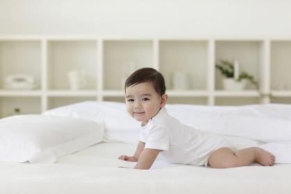 ベッドの上で腹ばいをしている赤ちゃん