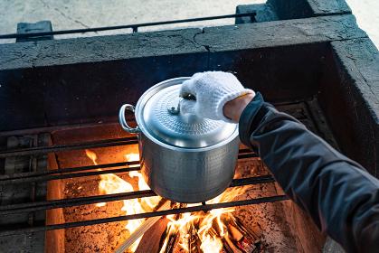キャンプ場の自炊風景 鍋に火をかける