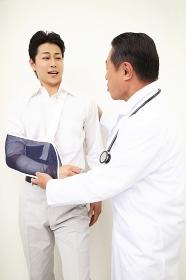 男性患者の骨折をねぎらう医者