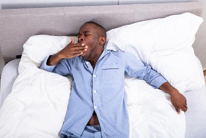 Sleepy Man Yawning On Bed