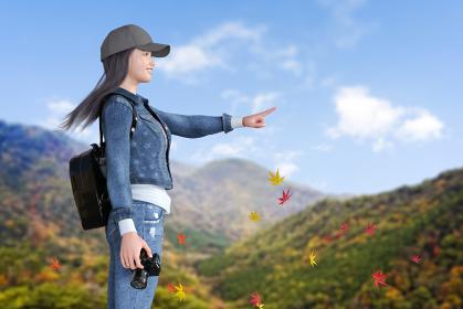 帽子をかぶった女の子が紅葉した山に登りカメラを片手に遠くの景色を指さす