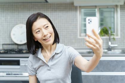 スマートフォンで自分を撮影するミドル女性