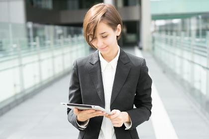 タブレットPCを持ってビジネス街を歩く女性