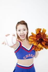 野球ボールを持って微笑むチアガール