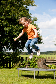 child on trampoline in the garden