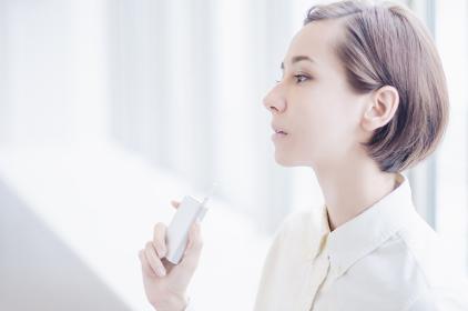 加熱式タバコを吸うショートヘアーの女性