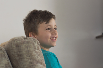 Young boy smiling using a blue t-shirt and looking to the side