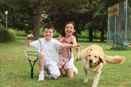 テニスウェアを着ている子供と犬