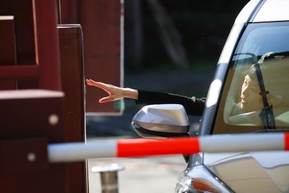 手を伸ばし駐車券を撮る女性