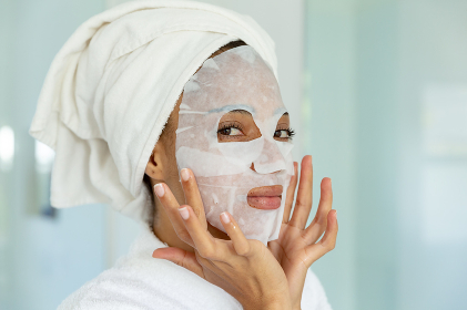 Mixed race woman wearing bathrobe and cleansing face mask in bathroom. staying at home in isolation during quarantine lockdown.