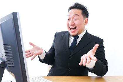 パソコンを見て驚くビジネスマン