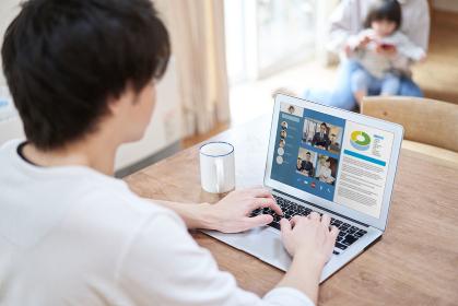 テレワークでオンラインミーティングをするアジア人男性