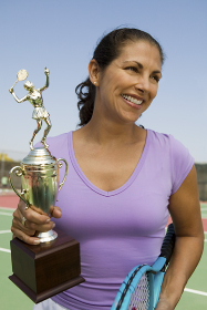 Mid-adult female tennis player on court holding trophy front view