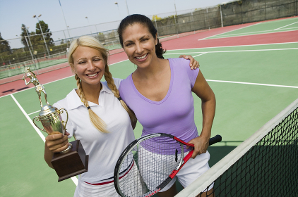 Two female Tennis Players by net on court holding trophy portrait