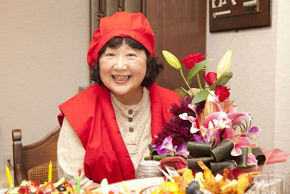 赤い服で祝う還暦女性