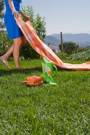 Woman preparing picnic in park, leg-view