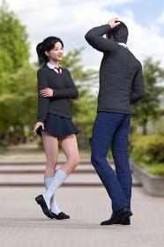 グランド脇の花壇で赤いネクタイをしたグレーのセーターを着たクラスのマドンナ的女子高生と照れながら話す