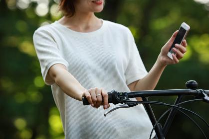 スマートフォンを操作しながら自転車に乗る女性