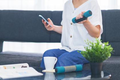 外出を控えて自宅リビングでダンベル運動でダイエットに励む中年女性【ウィズコロナのニューノーマル】