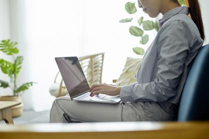 リビングでパソコンを使用する若い女性