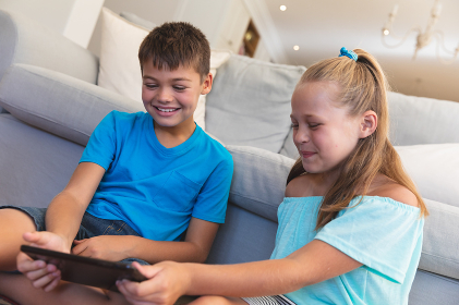 Caucasian brother and sister smiling and using tablet at home. childhood with technology, spending free time at home.