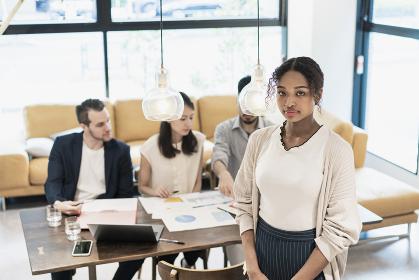 オフィスでポーズをするビジネスウーマンと国際色豊かなビジネスチーム
