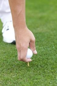 ゴルフボールをセットする男性の手元