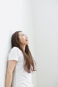 壁に寄り掛かる白いTシャツの若い日本人女性