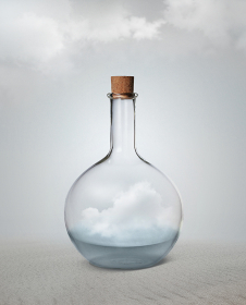 Small vintage glass bottle with water and cloud inside standing among desert.