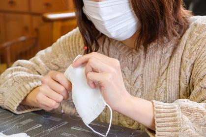 子供用マスクに紐を通す女性 手作り 感染症対策