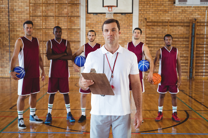 Confident coach and basketball player standing in the court