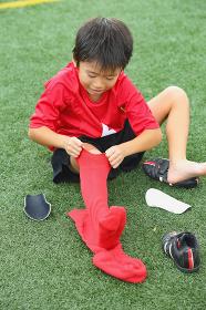 靴下を履くサッカー少年
