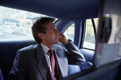 タクシーの車内で電話をするビジネスマン