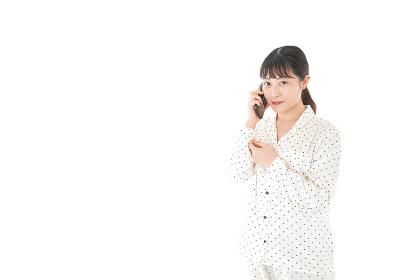 パンジャマでスマホを使う若い女性