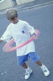 Portrait, Ganzfigur, 8 Jahre alter blonder Junge bekleidet mit weissem T-Shirt und blauen Shorts spielt auf der Strasse mit einem Hoolahoop Reifen