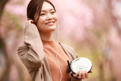 CDプレーヤーで音楽を聴く女性