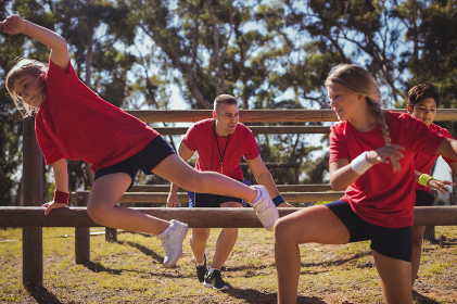 Trainer instructing kids during obstacle course training