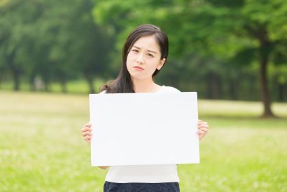 ホワイトボードを持つ女性 考える