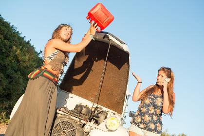 Girls near a car with no fuel.