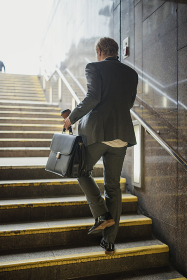 Businessman walking up the Stairs in the Train Station